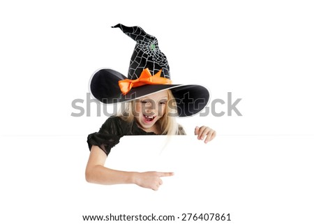 Beautiful smiling little girl with long blonde hair in the witch costume pointing the sign. Black witch hat with web, spider and orange bow. Copy space. - stock photo