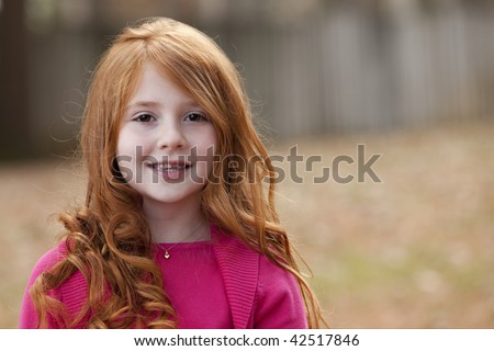 Beautiful smiling little girl with long red hair in pink sweater - stock photo