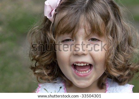 Beautiful smiling little three-year-old girl with bouncy natural curly hair held back with a pink bow. - stock photo