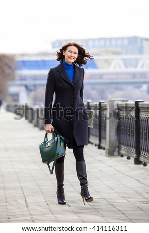 beautiful smiling middle-aged woman in a dark coat goes on embankment and hold in his hands of a green handbag and a laptop