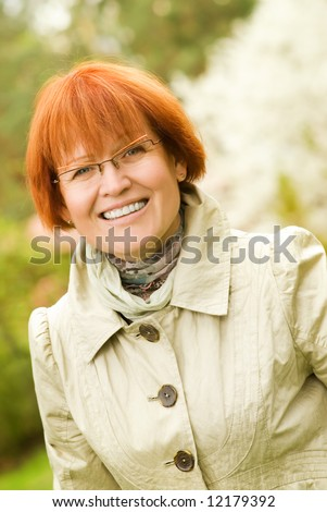 Beautiful smiling middle-aged woman outdoors - stock photo
