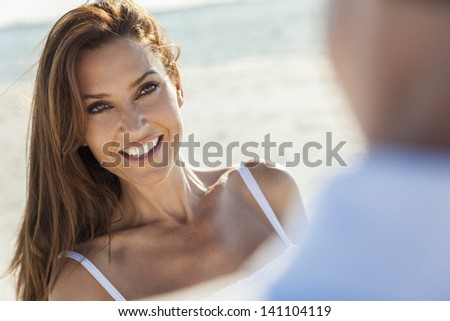 Beautiful smiling middle aged woman with man couple together in sunshine on a beautiful tropical beach - stock photo