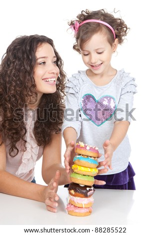 beautiful smiling mother and little daughter eating colorful donuts over white background