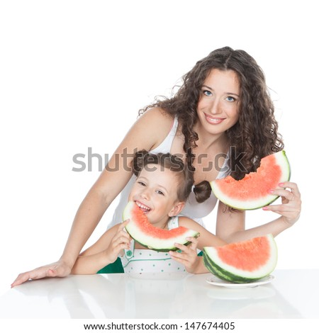 Beautiful smiling mother and little daughter eating watermelon over white background - stock photo