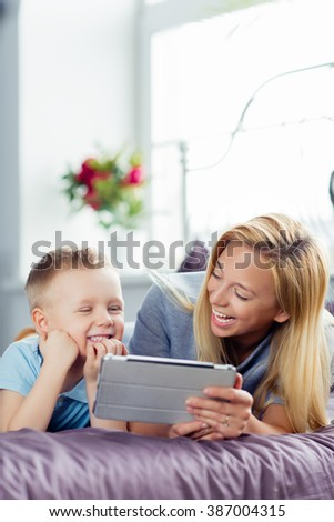 Beautiful smiling mother and son playing with digital tablet laying on bed. - stock photo