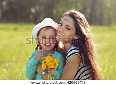 Beautiful smiling mother embracing her daughter with yellow bright flowers on summer background - stock photo