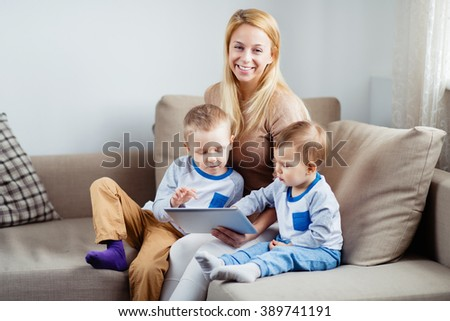 Beautiful smiling mother with her sons playing digital tablet - stock photo