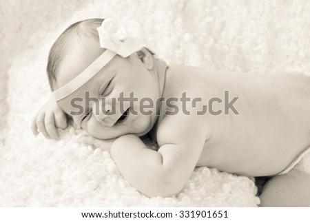 Beautiful smiling newborn baby girl sleeping on a blanket - stock photo