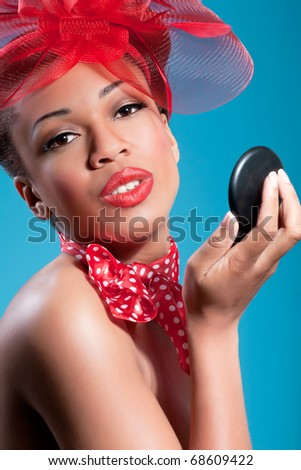Beautiful smiling pinup girl holding a mirror and checking makeup - stock photo