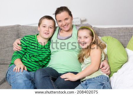 Beautiful smiling pregnant mother with her children