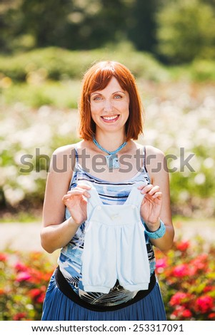 Beautiful smiling pregnant woman with baby clothes outdoor