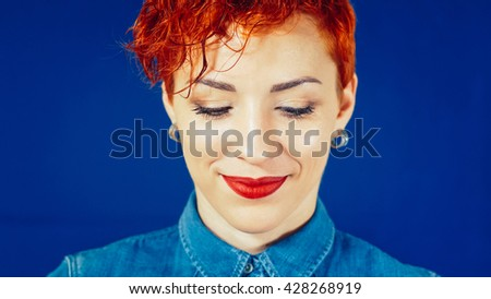 Beautiful smiling red-hair woman portrait with short hair on blue background. Young girl smiling and looking down. Stylish elegant woman with red lips. Beauty fashion make-up portrait. - stock photo