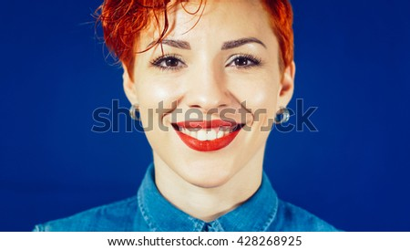 Beautiful smiling red-hair woman portrait with short hair on blue background. Young girl smiling and looking at camera. Stylish elegant woman with red lips. Beauty fashion make-up portrait. - stock photo