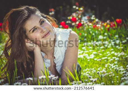 Beautiful smiling red-haired young woman lying on grass against summer green park.