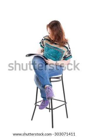 Beautiful smiling redhead plus size wreckled model with folder and ballpoint pen sitting on the bar chair. Isolated on a white background. - stock photo