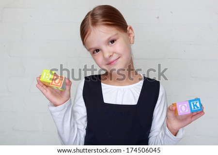 Beautiful smiling schoolgirl puts words from children's blocks with the letters/Charming child playing with cubes of Latin letters - stock photo