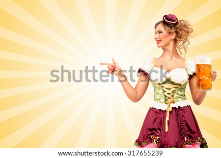 Beautiful smiling sexy Oktoberfest waitress wearing a traditional Bavarian dress dirndl holding beer mug, and pointing aside on colorful abstract cartoon style background. - stock photo