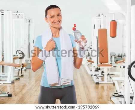 beautiful smiling sportswoman holding bottle of water and looking at camera - stock photo