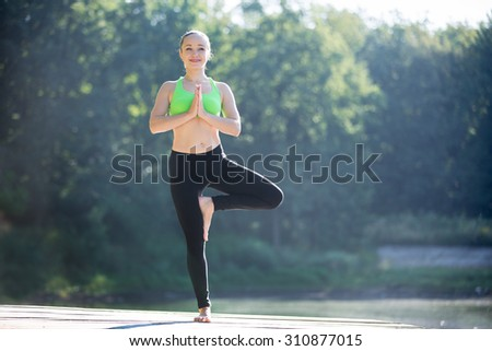 Beautiful smiling sporty fit blond young woman in green sportswear working out outdoors on summer day, standing in Tree posture (Vrikshasana), full length - stock photo