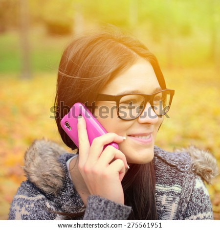 Beautiful smiling student girl talking on cell phone  - stock photo