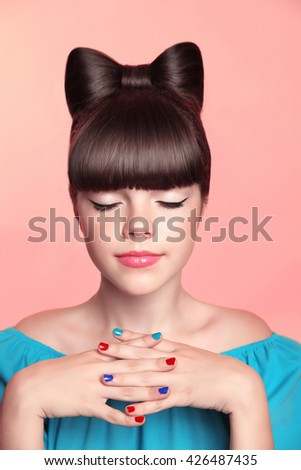Beautiful smiling teen girl with bow hairstyle, makeup and colorful manicured polish nails. Funny girl in blue dress showing manicure fingers isolated on studio background. - stock photo