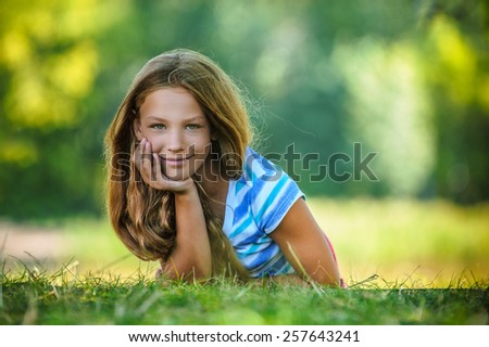 Beautiful smiling teenage girl in blue blouse lying on grass, against green of summer park.