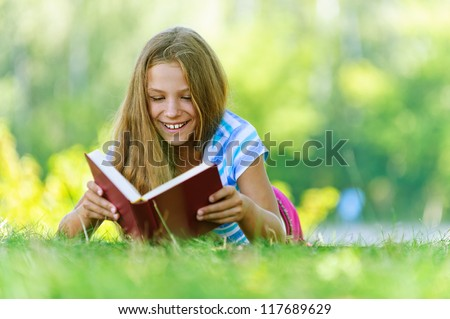 Beautiful smiling teenage girl in blue blouse lying on grass and read book, against green of summer park. - stock photo
