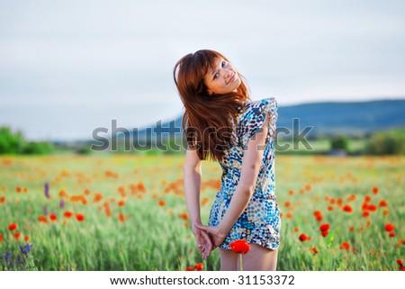 Beautiful smiling teenage girl posing in poppy field - stock photo