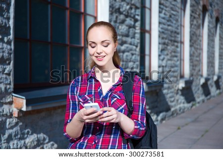 beautiful smiling teenage student girl with smart phone and backpack - stock photo