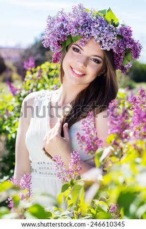 Beautiful smiling teenager girl is wearing beautiful wreath of lilac flowers - stock photo