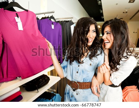 Beautiful smiling twin females at fashion boutique, looking at clothes - stock photo