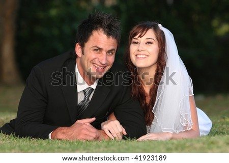 Beautiful smiling wedding couple laying down outdoors on the grass