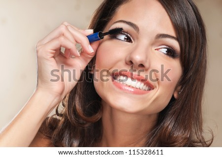 Beautiful smiling woman applying mascara on her eyelashes - stock photo