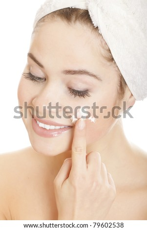 Beautiful smiling woman applying moisturizer cream on her face. Isolated on white background - stock photo