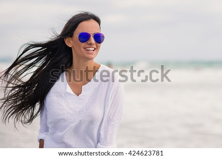 Beautiful smiling woman close up portrait on the beach.