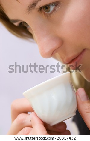Beautiful smiling woman drinking coffee close-up