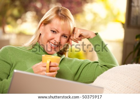 Beautiful, Smiling Woman Enjoys Her Warm Drink and Laptop Relaxing Day. - stock photo