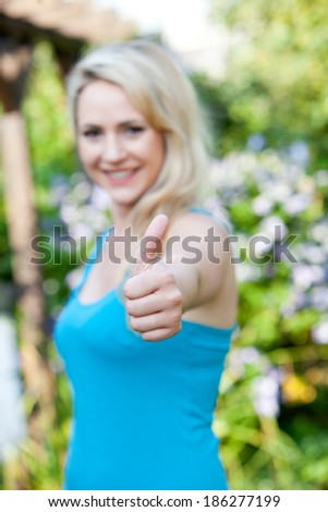 Beautiful smiling woman giving a thumbs up gesture of approval, agreement and success as she stands outdoors in a summer garden, focus to her hand - stock photo