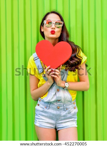 Beautiful smiling woman holding a red heart over green background. Fashion portrait stylish pretty woman in sunglasses outdoor. - stock photo