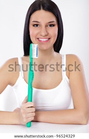 Beautiful smiling woman holding big toothbrush, concept- dental hygiene