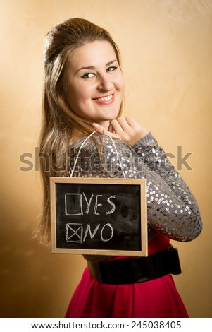 Beautiful smiling woman holding blackboard with two answers - stock photo