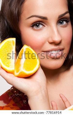 Beautiful smiling woman holding orange halves in hand - stock photo