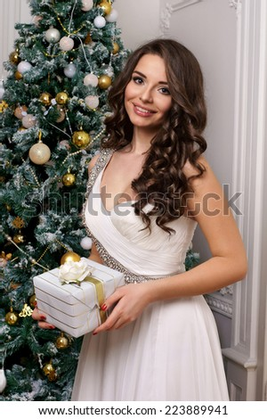 Beautiful smiling woman holding white giftbox in christmas interior. Fashion style portrait