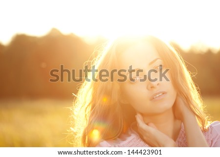 Beautiful smiling woman in a field at sunset