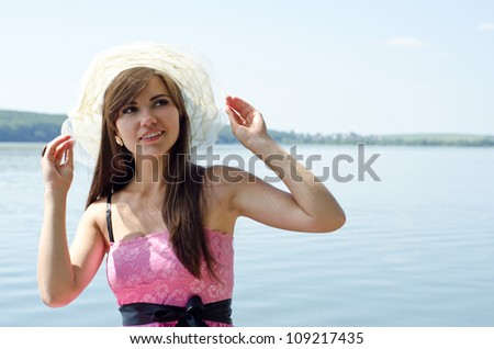beautiful smiling woman in a hat on the lake - stock photo