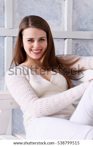 Beautiful smiling woman in a white knitted sweater