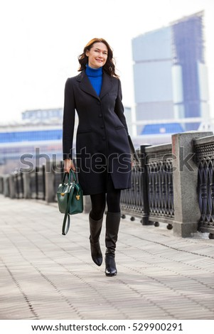 beautiful smiling woman in dark coat with handbag and laptop goes on quay on background of skyscrapers business district. fashion style