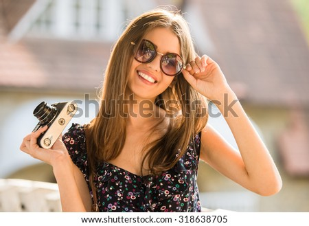 Beautiful smiling woman in dress and sunglasses is holding old fashioned camera, outdoors. - stock photo
