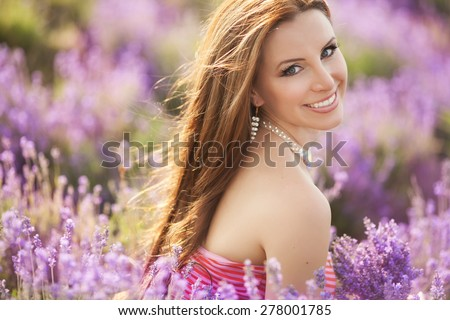 Beautiful smiling woman in lavender field, Beauty girl with lavender flowers, female outdoor portrait,summer time, series  - stock photo