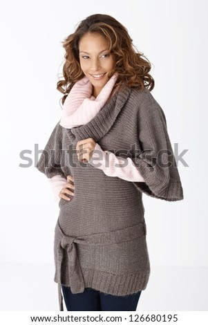 Beautiful smiling woman in warm clothes over white background.